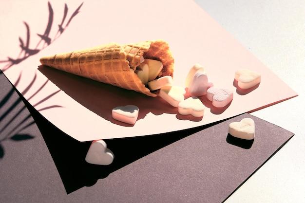 Zuckerherzen in eiswaffelkegel auf sahne und grauem geometrischem schichtpapier