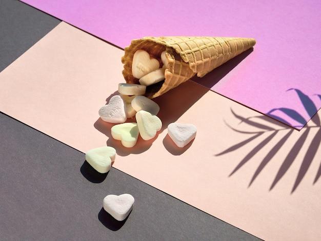 Zuckerherzen in eiswaffeltüte auf lila, cremefarbenem und grauem schichtpapier