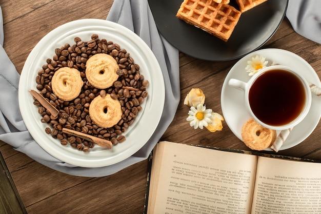 Zuckerkekse auf kaffeebohnen in einer untertasse und einer tasse tee.