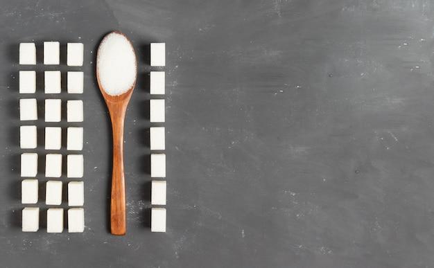 Zuckerklumpen mit einem hölzernen öko-löffel gefüllt mit losem zucker auf einem grauen hintergrund