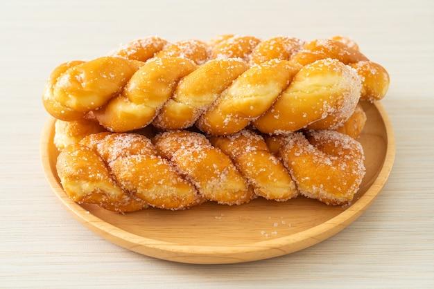 Zuckerkrapfen in spiralform auf holzteller