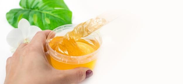 Zuckerpaste in einem transparenten glas auf weißem hintergrund ein meister rührt die zuckerpaste vor dem entfernen...