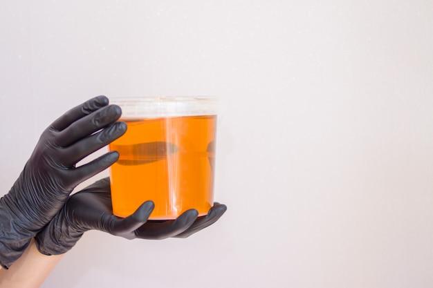 Zuckerpaste oder wachshonig für das haar, das mit schwarzen handschuhhänden von cosmetologist im badekurortsalon entfernt