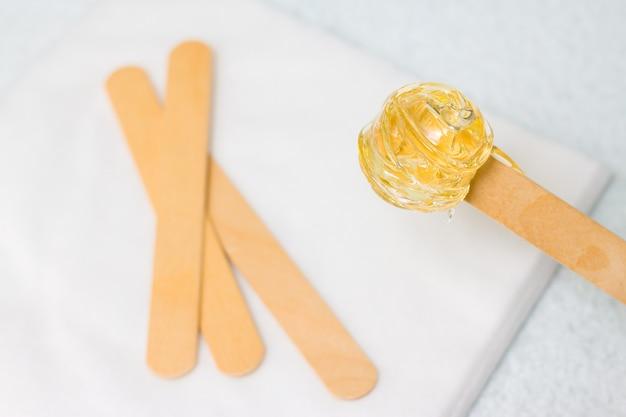 Zuckerpaste oder wachshonig zum entfernen der haare mit holzspatelstäbchen aus holz