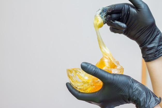 Zuckerpaste oder wachshonig zum entfernen der haare mit schwarzen handschuhen - enthaarung und schönheit