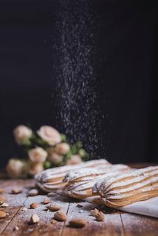 Zuckerpulver, das auf dem gebackenen eclair mit mandeln gegen schwarzen hintergrund abwischt