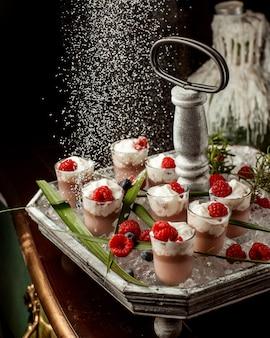 Zuckerpulver wird über schokoladenpuddinggläser gestreut