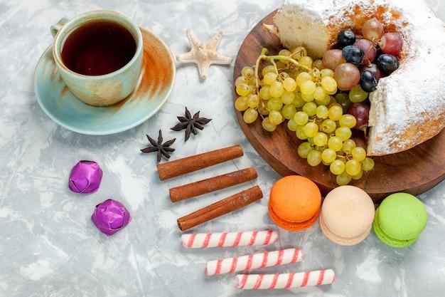 Zuckerpulverkuchen mit halber draufsicht mit frischen trauben, macarons, zimt und tee auf weißem zuckerkuchen mit obstkuchen