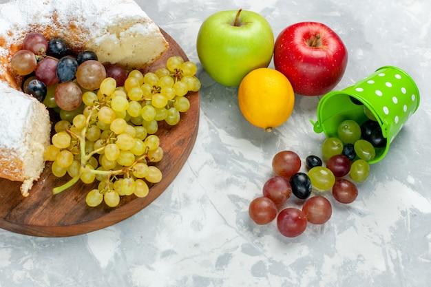 Zuckerpulverkuchen mit halber draufsicht mit frischen trauben und äpfeln auf weißem schreibtisch-obstkuchen-keks-süßem zuckerauflauf