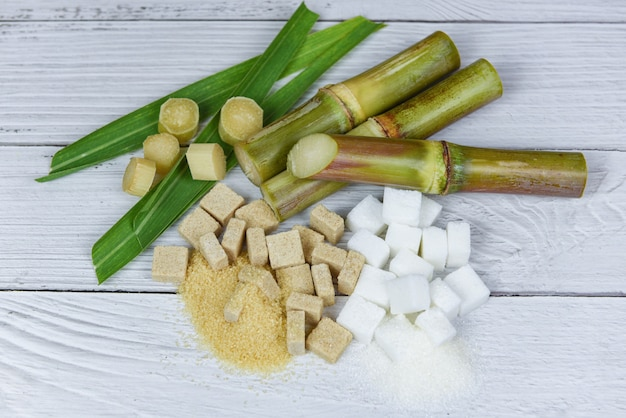 Zuckerrohr mit den braunen und würfeln des raffinierten zuckers auf hölzernem hintergrund