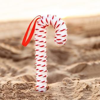 Zuckerstange der weißen weihnacht bei sonnenuntergang auf sandigem strand