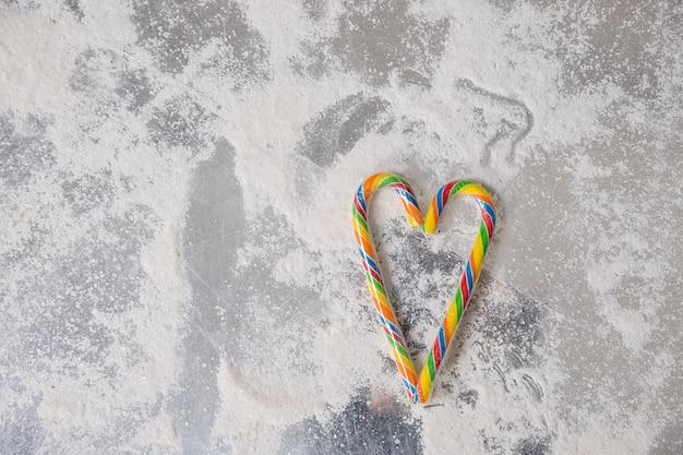 Zuckerstangen in einer herzform gegen den weißen hintergrund, zum des valentinsgrußkonzeptes zu übermitteln. lutscher. candy valentinstag herzen