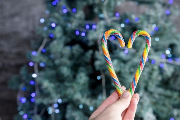 Zuckerstangen in form des herzens. weihnachtsbaum. mitternacht. retro-stil. frohe weihnachten oder guten rutsch ins neue jahr-konzept. grußkarte