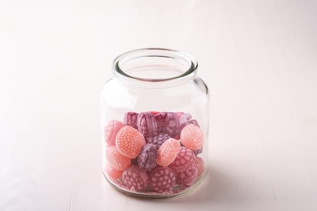 Zuckerstangenbonbons in form von saftigen beeren im glas auf weißem hölzernem hintergrund lokalisiert