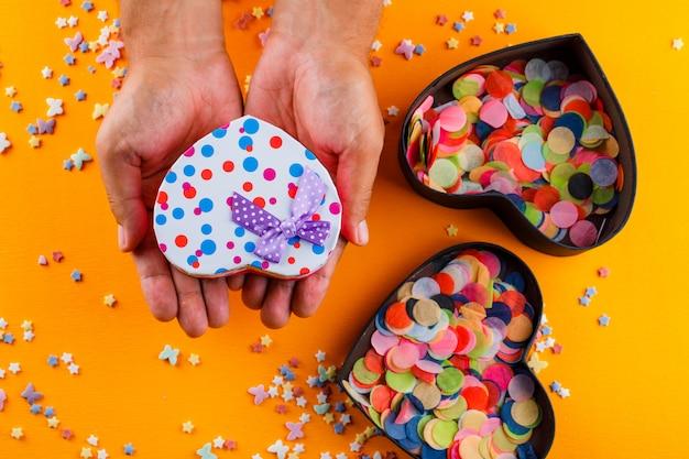 Zuckerstreusel, konfetti in kisten auf gelbem tisch und männchen mit geschenkbox.