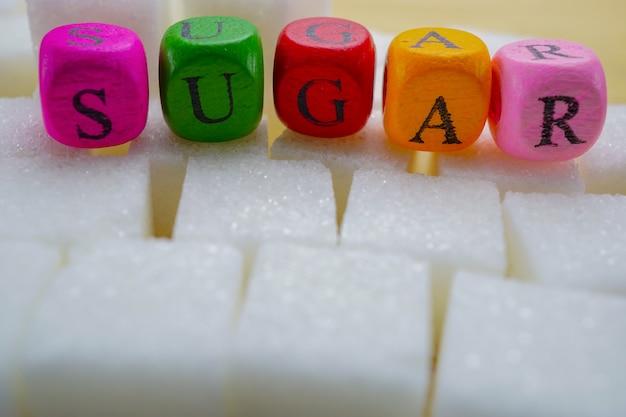 Zuckersüße würfel mit bunten hohen kalorien des englischen alphabetes: gesunder nahrungsmittelbetrug der fetten diät