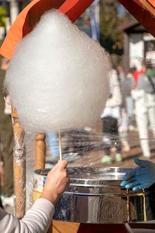 Zuckerwatte auf der straße kaufen süßigkeiten machen straßenbonbons süße am stiel in der hand