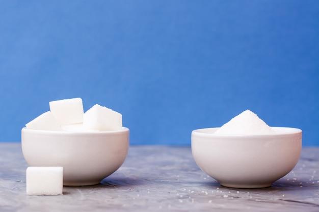 Zuckerwürfel und kristallzucker in den weißen schüsseln auf einer tabelle