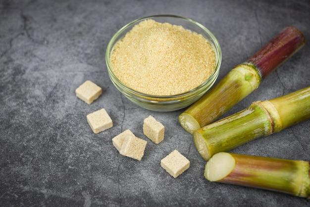 Zuckerwürfel zuckerrohr und brauner zucker in der schüssel und im dunklen tabellenhintergrund