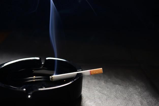 Zündete zigarette mit rauch auf einem leeren schwarzen aschenbecher liegend