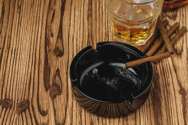 Zündete zigarre in einem aschenbecher aus der nähe an