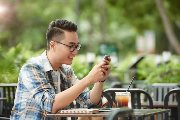 Zufällig gekleideter junger asiatischer mann, der café am im freien sitzt und smartphone verwendet