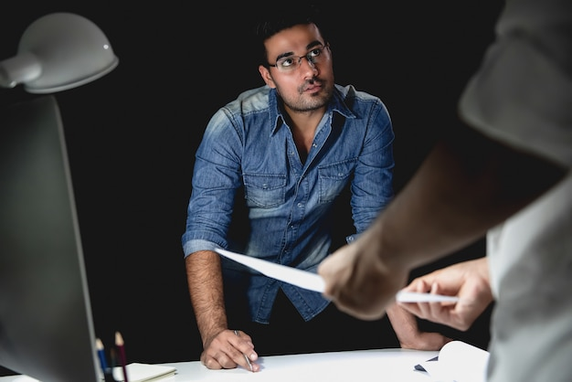 Zufällige asiatische architekten, die spät nachts arbeiten, projekt in der sitzung besprechend