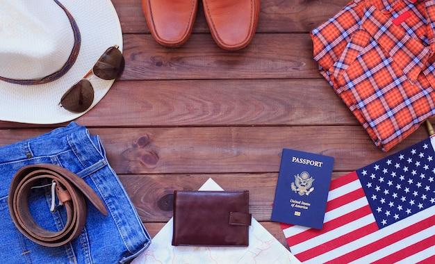 Zufällige ausstattungen der männer mit mannkleidung, reisevorbereitungen und zubehör auf hölzernem hintergrund