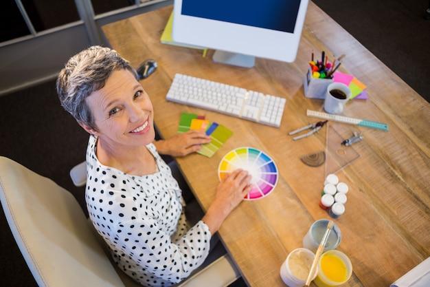 Zufällige geschäftsfrau, die mit farbkarte arbeitet