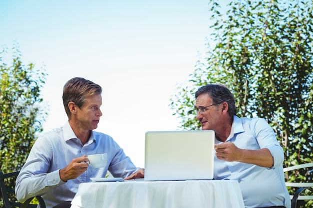 Zufällige geschäftsmänner, die kaffee trinken und laptop verwenden