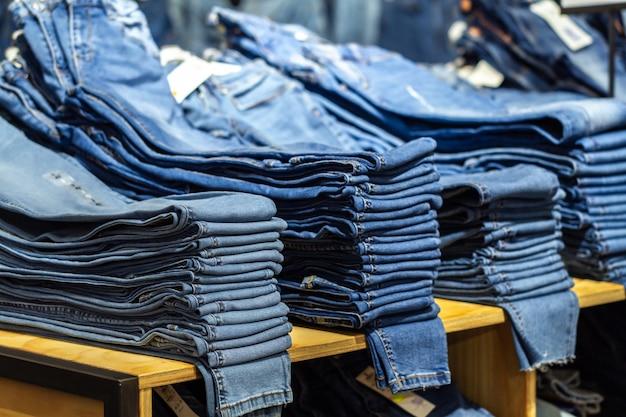 Zufällige jeans auf gebrauchtmarkt im speicher. kaufendes einkaufszentrum der beiläufigen kleidung in mode, neue kleidung für wandschrank wählend