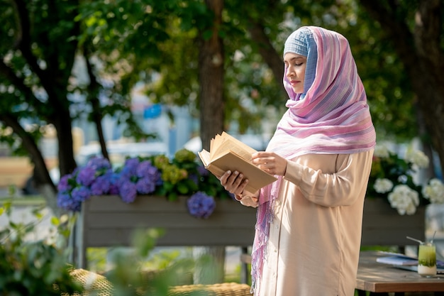 Zufällige junge frau im hijab, die durch buch schaut, während sie zeit im park oder in der terrasse verbringt