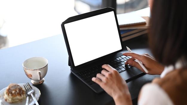 Zufällige junge frau mit dem stift, der auf digitalem tablett am café arbeitet.