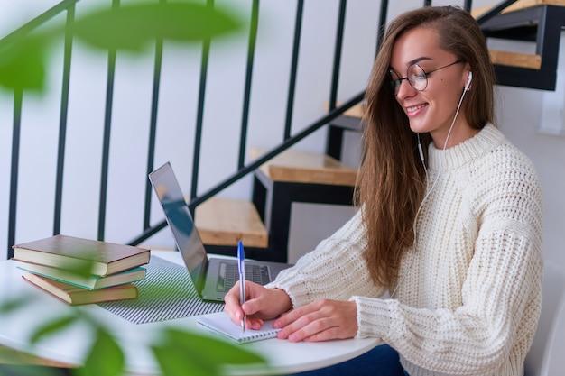 Zufällige junge lächelnde kluge studentin in kopfhörern, die mit dem lernen der fremdsprache zufrieden sind. frau macht notizen am notizbuch während des betrachtens von webinar-videokursen. online-ausbildung