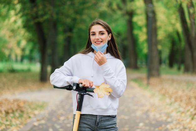 Zufällige kaukasische frau, die schützende gesichtsmaske trägt, die städtischen elektroroller im stadtpark während der covid-pandemie reitet. konzept der städtischen mobilität.