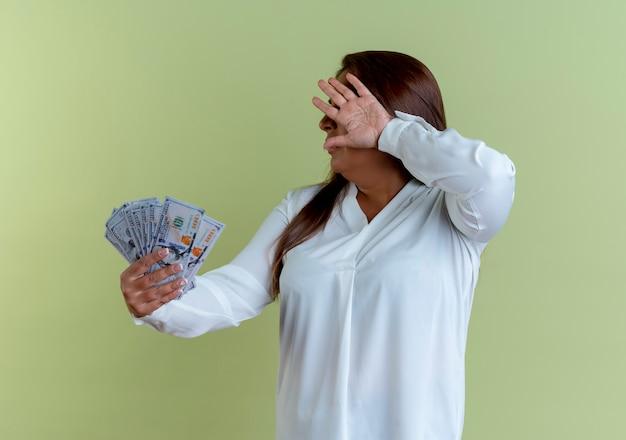 Zufällige kaukasische frau mittleren alters, die geld und bedecktes gesicht mit hand hält