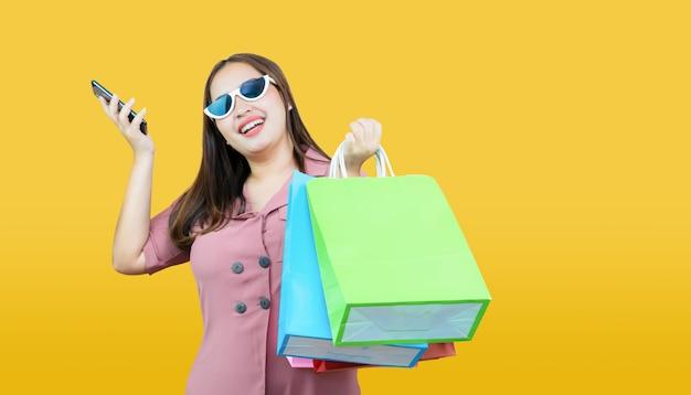 Zufällige kleidung der glücklichen asiatischen frau, die kreditkarte und einkaufstaschen auf hellgelbem hält.