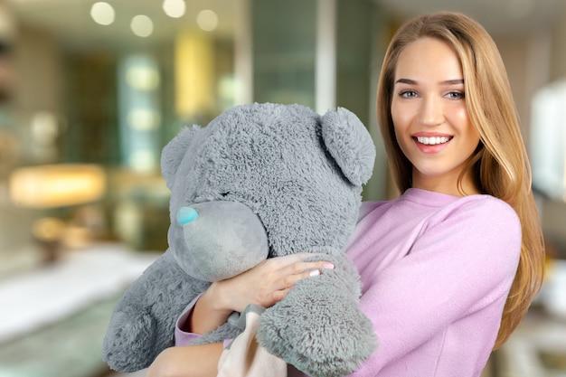 Zufällige lächelnde junge frau, die teddybären hält