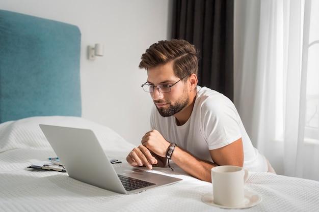 Zufälliger erwachsener mann, der genießt, zu hause zu arbeiten