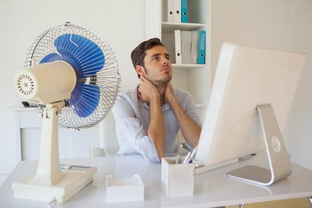 Zufälliger geschäftsmann, der am schreibtisch mit elektrischem ventilator sitzt