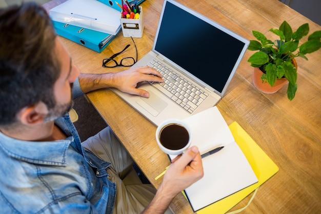 Zufälliger geschäftsmann, der an seinem schreibtisch arbeitet und tasse kaffee hält