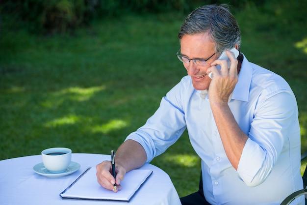 Zufälliger geschäftsmann, der kenntnisse nimmt und einen telefonanruf hat