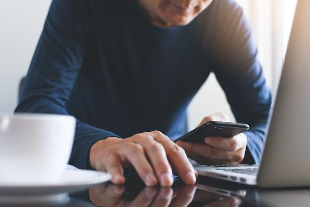 Zufälliger geschäftsmann, der mobiles smartphone verwendet und an laptop-computer auf bürotisch arbeitet