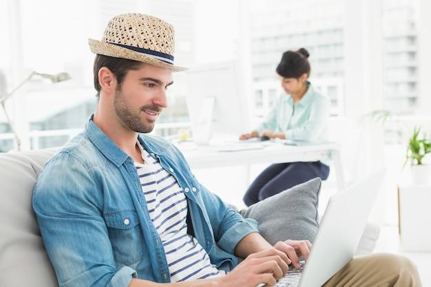Zufälliger geschäftsmann unter verwendung des laptops auf couch