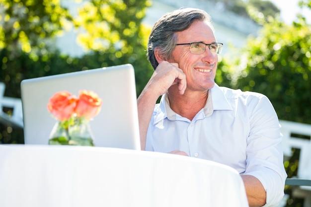 Zufälliger geschäftsmann unter verwendung des laptops träumend