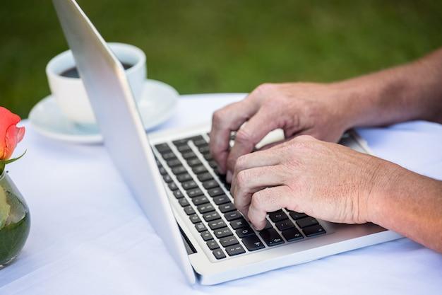 Zufälliger geschäftsmann unter verwendung des laptops und trinken des kaffees