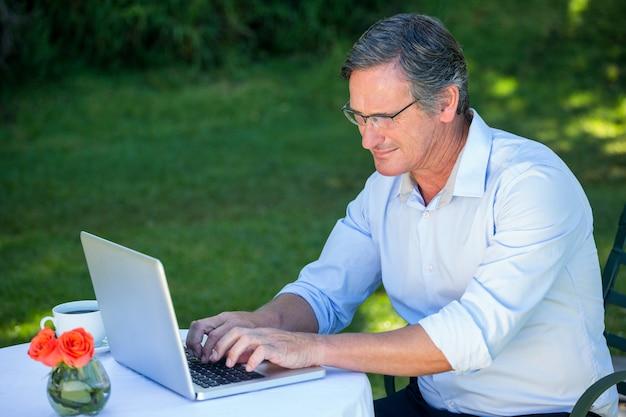 Zufälliger geschäftsmann unter verwendung des laptops