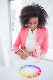 Zufälliger grafikdesigner, der an ihrem schreibtisch skizzieren arbeitet