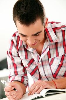 Zufälliger junger mann, der auf notizbuch schreibt