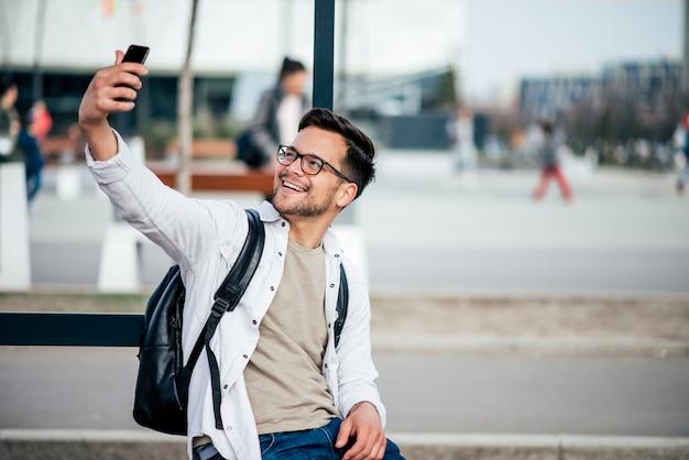 Zufälliger junger mann, der selfie am intelligenten telefon an der stadtstraße nimmt.